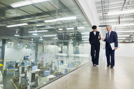 Managers walking and talking in factory