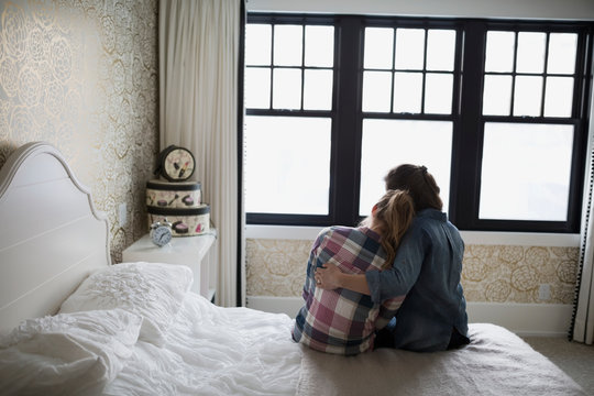 Mother hugging teenage daughter in bedroom