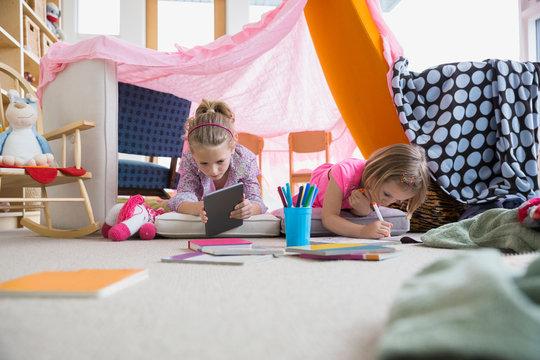 Girls coloring inside living room fort