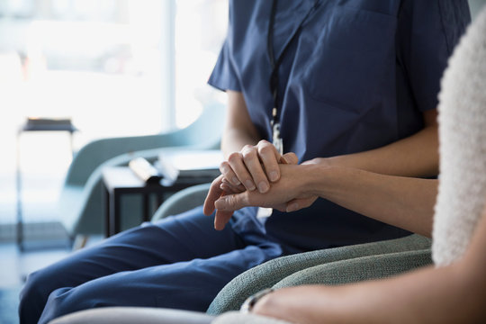 Nurse holding patientΠ hand in clinic lobby