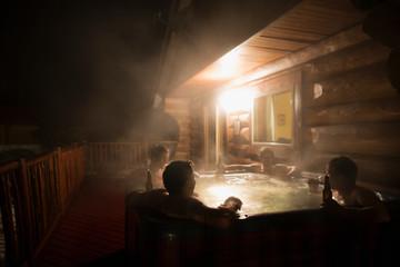 Men drinking beer hot tub on cabin deck
