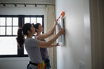 Mother and teenage daughter hanging art level tool
