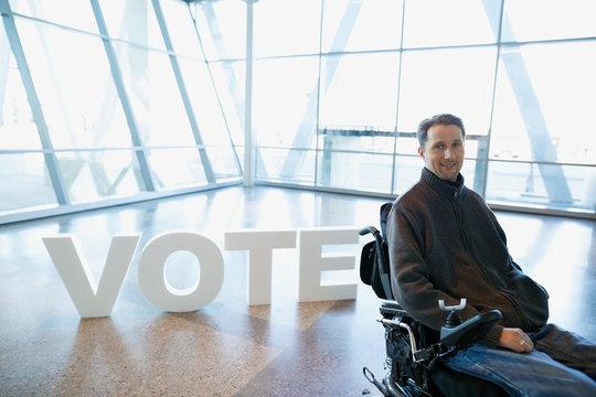 Portrait smiling man in wheelchair near Vote text