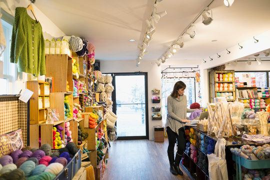 Yarn store owner working on laptop