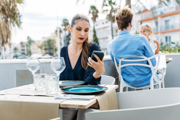 boring young girl waiting for her date sitting at a table in an outdoor restaurant