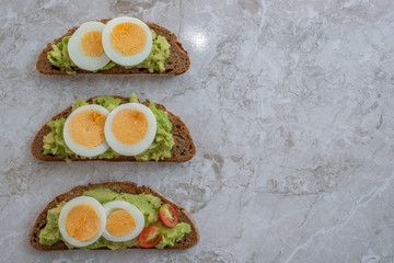 sliced avocado and egg on toasted bread for healthy breakfast or snack