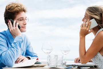 Young couple in the restaurant talking on the phone, phone addict concept