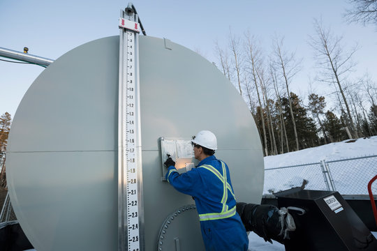 Male worker examining storage tank at gas plant