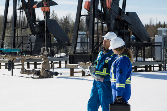 Workers discussing paperwork at drilling rigs in snow