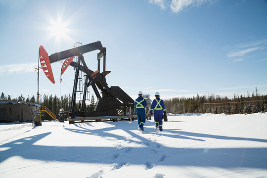 Workers walking toward drilling rigs in snow