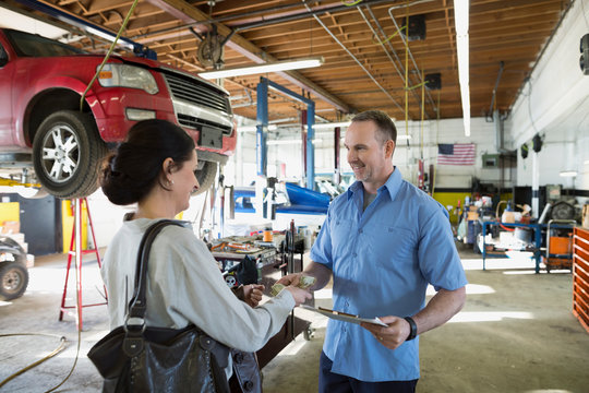 Customer paying mechanic with cash auto repair shop
