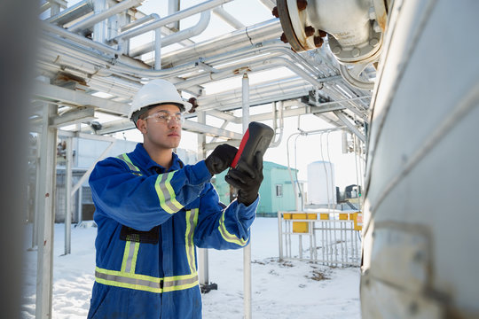 Male worker using wireless device at gas plant