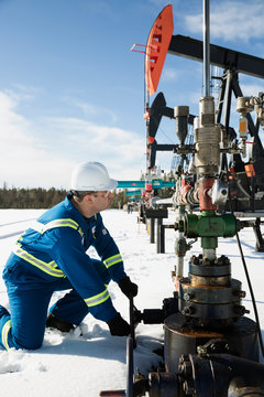 Male worker turning drilling rig valve in snow