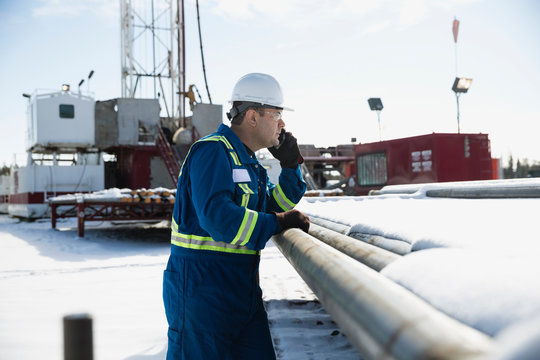 Male worker talking cell phone snowy gas plant