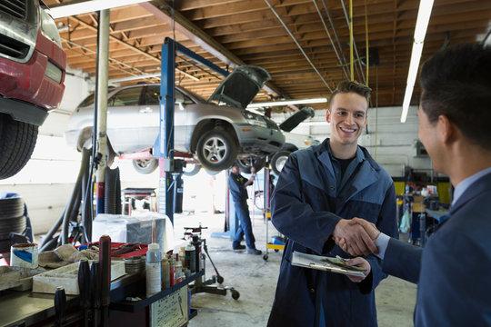 Mechanic and customer shaking hands auto repair shop