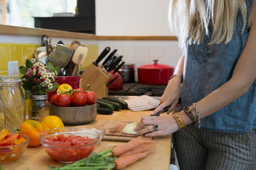 Young woman slicing vegetables in kitchen