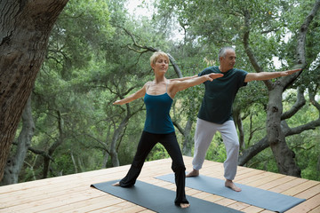 Couple practicing yoga warrior 2 pose on deck