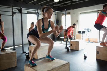 Focused woman jump squats in crossfit exercise class