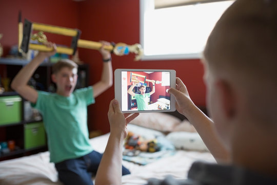 Boy photographing brother holding trophy with digital tablet