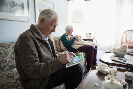 Senior couple playing solitaire on digital tablet and knitting in living room