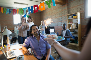 Coworker serving creative businessman birthday donut with sparkler