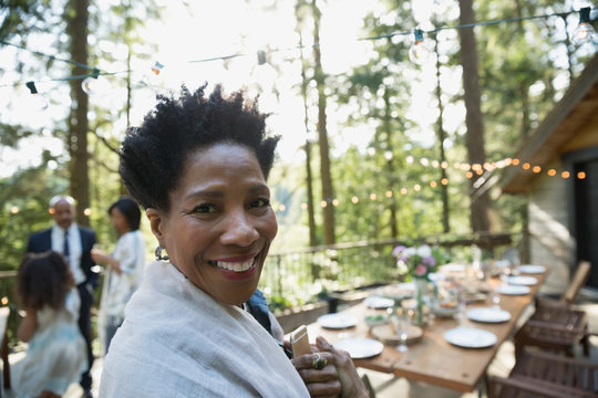 Portrait smiling woman on cabin balcony in woods