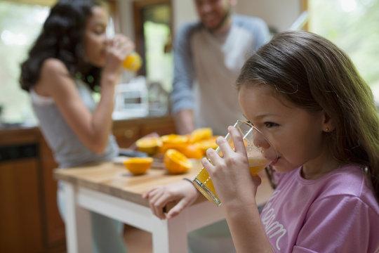 Girl drinking fresh squeezed orange juice in kitchen