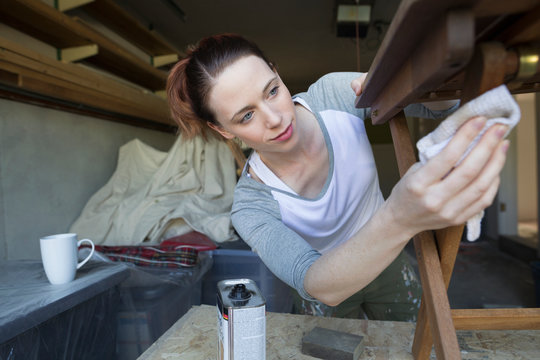 Woman staining wood furniture home improvement project