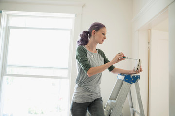 Woman on ladder changing smoke detector