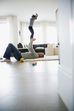 Father balancing daughter on hands in living room