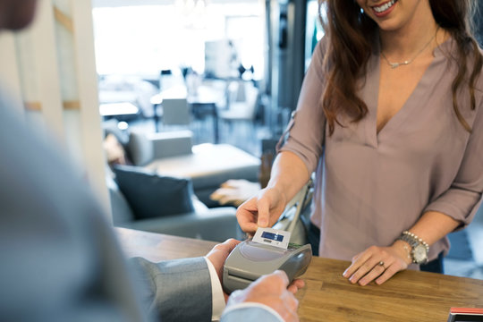 Woman paying using credit card reader in home furnishings store