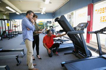 Salesman helping couple shopping for treadmill in home gym equipment store