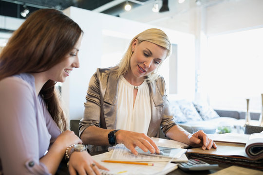 Interior designer and woman using digital tablet in home furnishings store