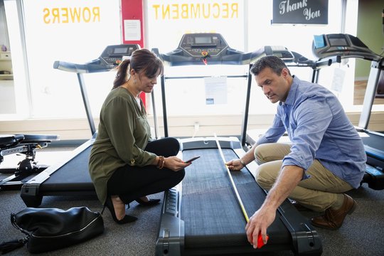 Couple measuring treadmill at home gym equipment store