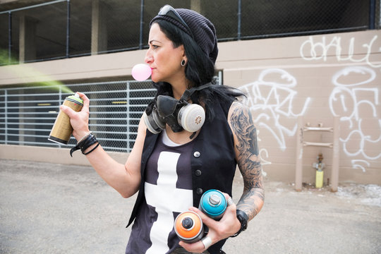 Cool mature female graffiti artist blowing bubble gum and spraying paint