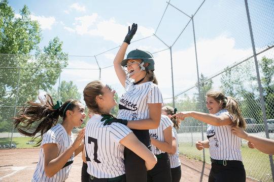 Enthusiastic middle school girl softball team celebrating on baseball diamond