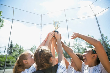 Middle school girl softball team holding trophy and cheering