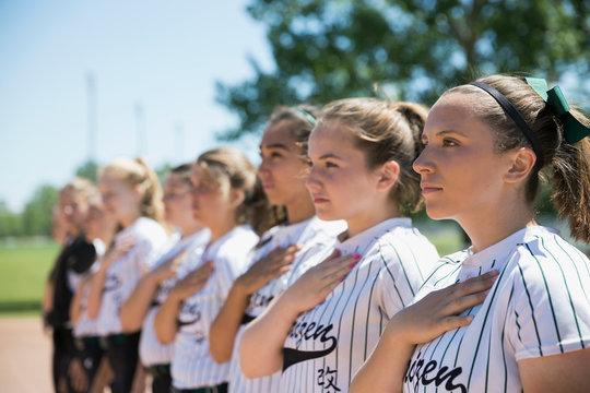 Middle school girl softball team pledging allegiance during national anthem