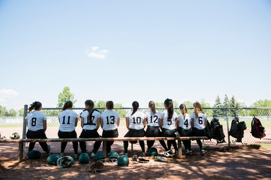 Middle school girl softball team sitting on bench