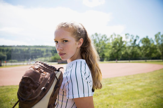 Portrait serious middle school girl softball player with baseball glove in outfield