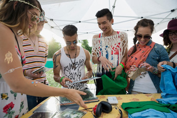 Young friends looking at merchandise in vendor booth at summer music festival