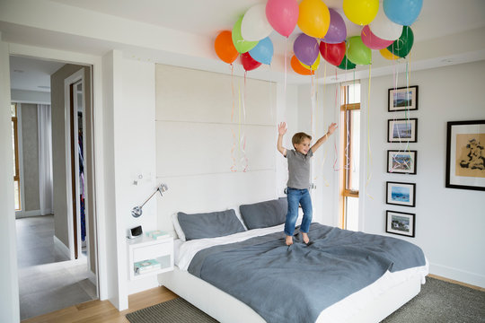 Boy jumping on bed below multicolor balloons