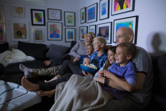 Family eating popcorn watching movie in dark living room