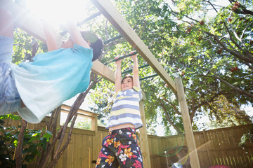 Boys playing on monkey bars in sunny backyard