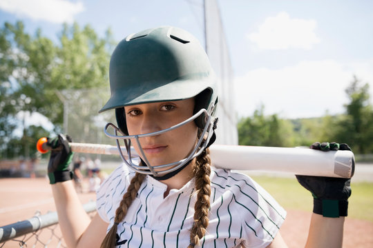 Portrait serious middle school girl softball player wearing batting helmet and holding bat