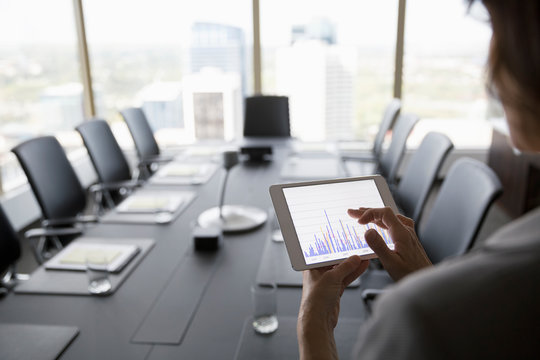 Businesswoman viewing bar chart on digital tablet in conference room