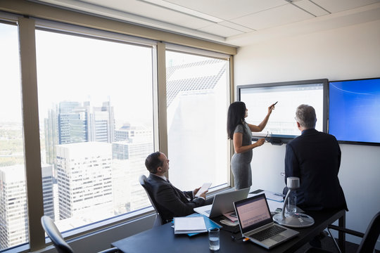 Business people meeting at large monitor in urban conference room