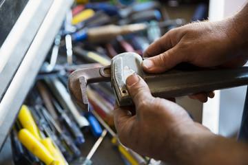 Close up male mechanic adjusting monkey wrench