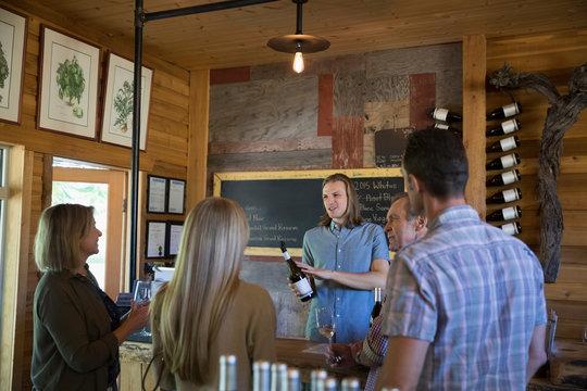 Vintner explaining wine to couples wine tasting in winery tasting room