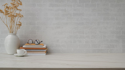 Cropped shot of workspace with copy space, vase, tea cup, eyeglasses and books on marble desk with ...